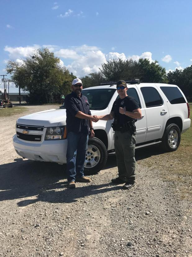 Quinton Police Chief Paul Moss, right, and Tim Cummings, Executive Vice President of Operations and Engineering with Red Mountain Energy shake hands in front of the donated vehicle.